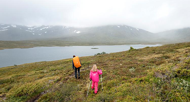 Två personer är ute och vandrar. Framför dem syns en sjö. Och bakom sjön är berg med snö på topparna.