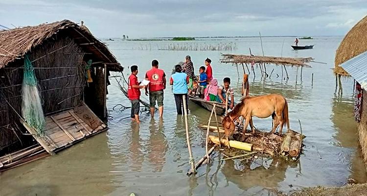 Bilden är tagen utomhus. Vattnet har stigit. Husen är i vatten. Det står några människor där.
