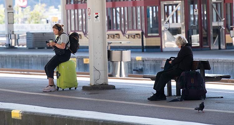 Vi ser en perrong på en station för tåg. En ung kvinna sitter på en väska. En äldre kvinna sitter på en bänk.