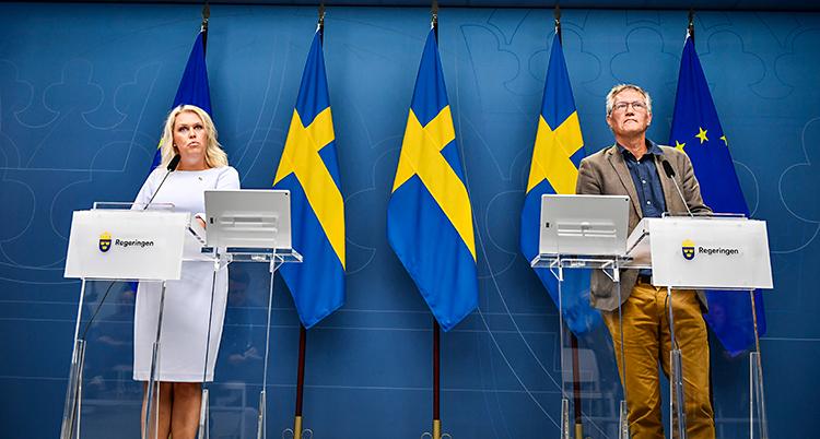 De står på en scen. Till vänster står Lena Hallengren. Till höger står Anders Tegnell. Bakom finns flera svenska flaggor.