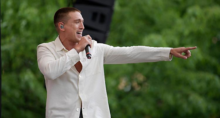 Han står på en scen och sjunger i en mikrofon. Han ler och pekar mot publiken. Han har på sig en vit skjorta.