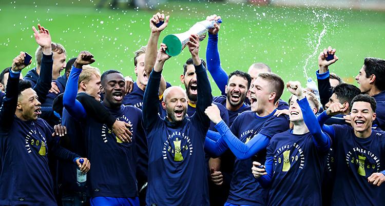 En massa män står på en fotbollsplan. De är glada. De hoppar och jublar. En av dem håller i en pokal.