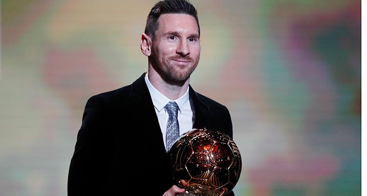 Fotbollsspelaren Lionel Messi håller i priset Guldbollen. Det ser ut som en rödsprakande fotboll.
