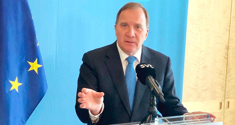 Stefan Löfven pratar på en presskonferens. I bakgrunden syns EUs flagga.