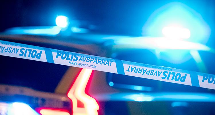 Bilden visar en polisavspärrning och blåljus från en polisbil.