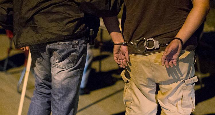Bilden visar en man som har blivit gripen av polisen och har handklovar på sig. Man ser bara mannens ryggtavla och händerna bakom hans rygg.
