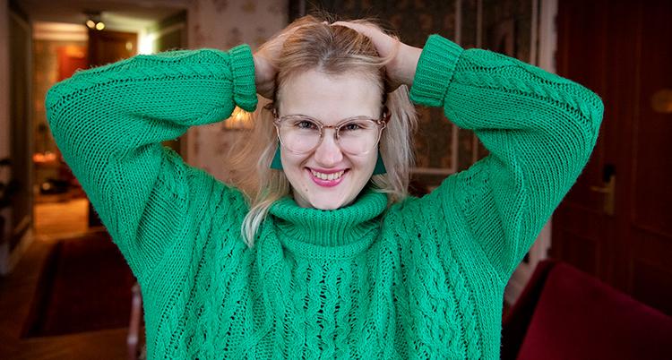 Emma Örtlund har på sig en grön tröja. Hon drar händerna genom håret.