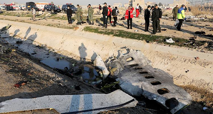 En del av flygplanet ligger på marken. I bakgrunden står en grupp människor.