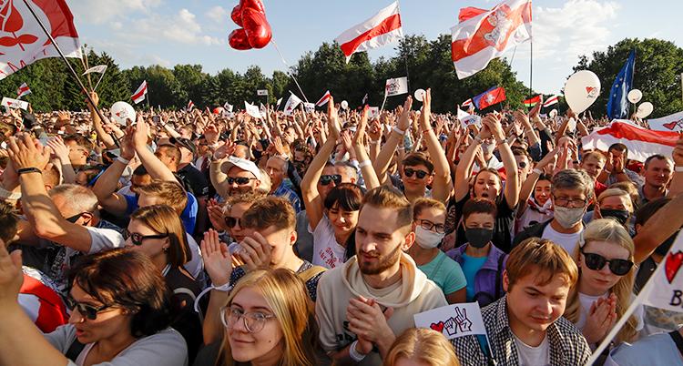 Många unga killar och tjejer går i ett demonstrationståg i Minsk i Vitryssland. Några viftar med ballonger och flaggor.