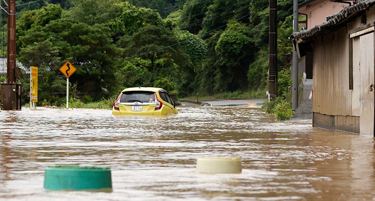 En gul bil flyter i vattnet på en gata som är helt översvämmad av vatten.