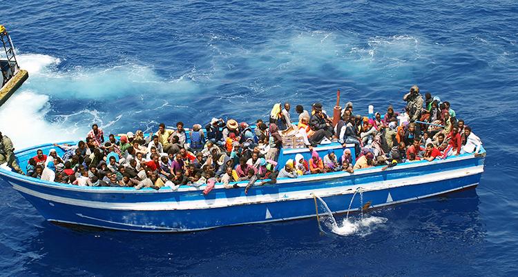 En båt är full med människor som flyr över Medelhavet till Europa.