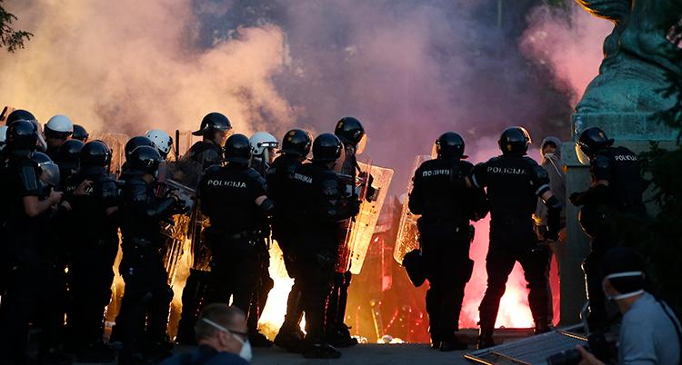 En grupp poliser vaktar en demonstration i Belgrad. I bakgrunden syns mycket rök.