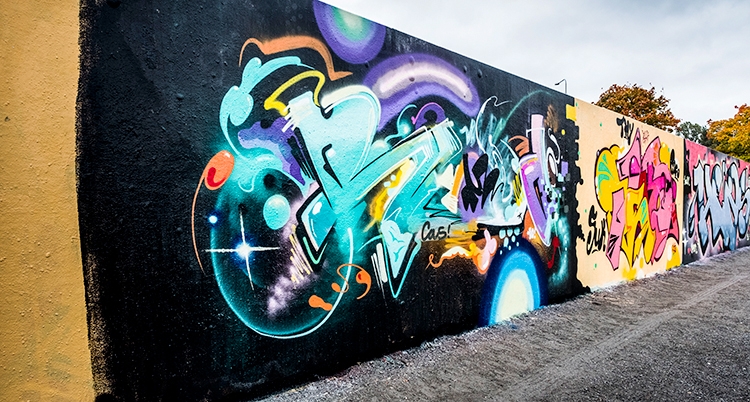 En vägg med graffiti i bland annat turkost och lila på en svart vägg.