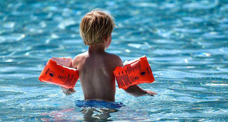 Ett barn står i en pool. Ryggen syns.