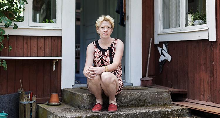 Hon sitter framför ett rött hus.