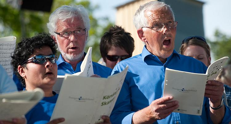 Flera personer i blå kläder sjunger i kör.