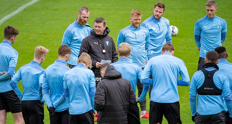 Spelare i träningskläder är samlade runt Malmös ledare.