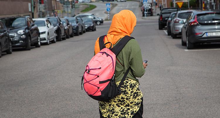 En kvionn med orange slöja och ryggsäck tittar på sin mobil. Hon har ryggen mot kameran.