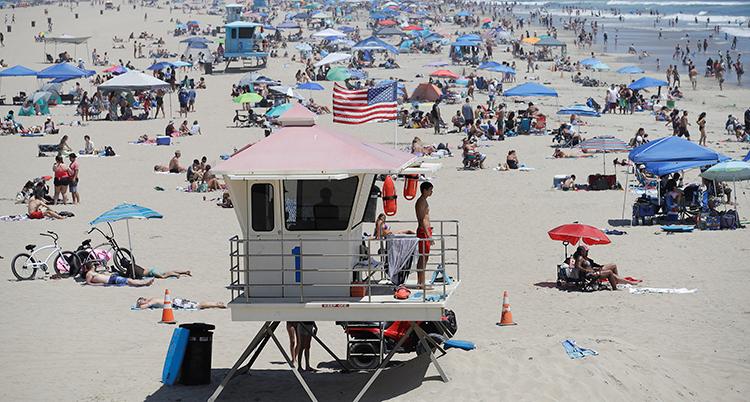 Många människor syns på stranden. De sitter med avstånd till varandra.
