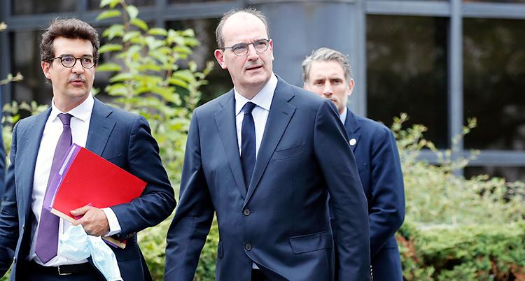 Frankrikes nya premiärminister Jean Kasta promenerar till ett möte med två andra män. Han har på sig en blå kavaj och slips.