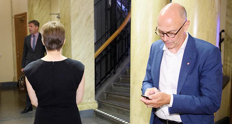 Två ledamöter under en paus under diskussionen. En tittar ner i sin mobiltelefon.
