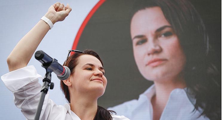Svetlana Tichanovskaja talar på ett valmöte. Hon har på sig en vit blus och höjer ena handen.