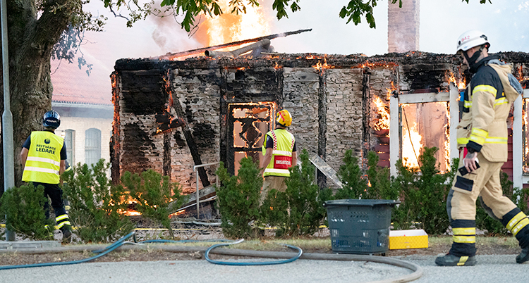 Räddningstjänsten jobbar med att släcka branden i en byggnad av trä.
