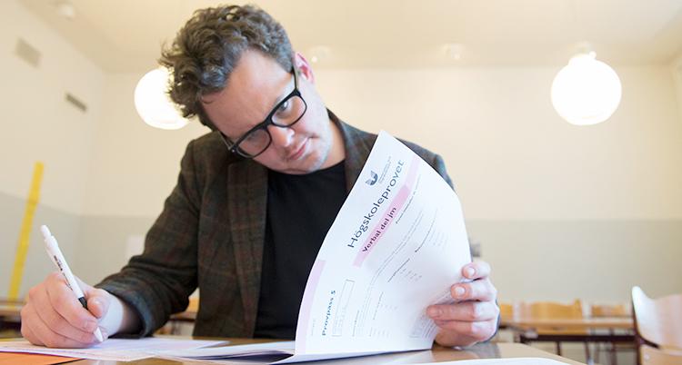 En man skriver ett högskoleprov i en skola.