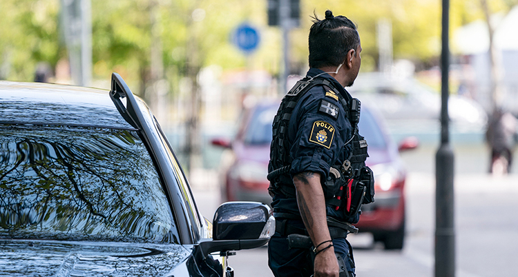 En polis står bredvid en bil.