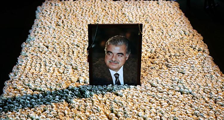 En bild av Libanons förre premiärminister Rafiq al-Hariri. Det är en bild på honom som står på hans grav. Graven är också täckt av blommor.