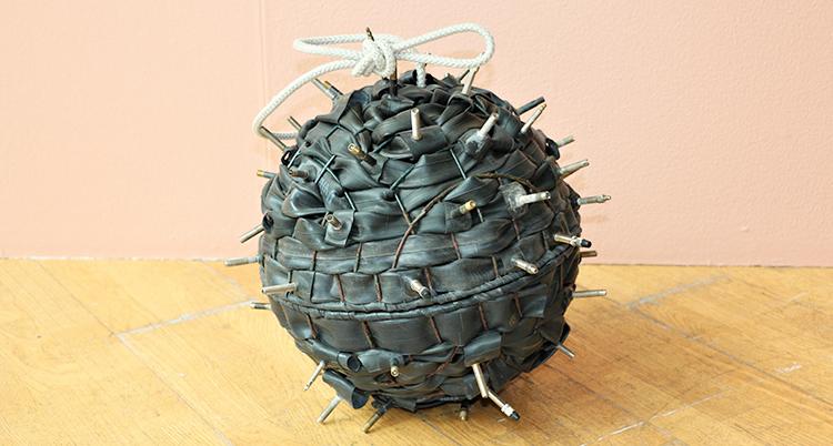 Ett konstverk som ser ut som viruset corona. Det är en rund boll med taggar. Färgen är gråaktig.