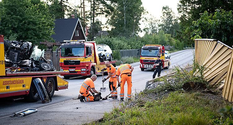 Bilden visar en väg i ett område med villor. Ett staket är trasigt. Några personer i orange kläder städar på vägen. Där finns också två trasiga bilar som står på bärgningsbilar.