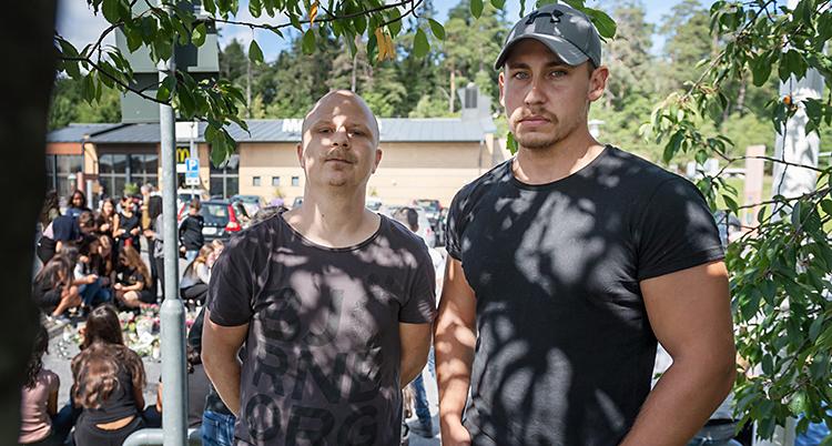 Bilden är tagen utomhus. Två män står och tittar allvarligt in i kameran. I bakgrunden syns en massa ungdomar som har samlats för att sörja.