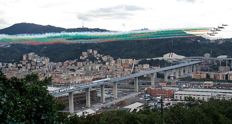 Vi ser en bro på långt avstånd. Runt om den finns hus. I bakgrunden är det berg. Över bron flyger flygplan. Efter dem kommer rök i färgerna röd, vit och grön.