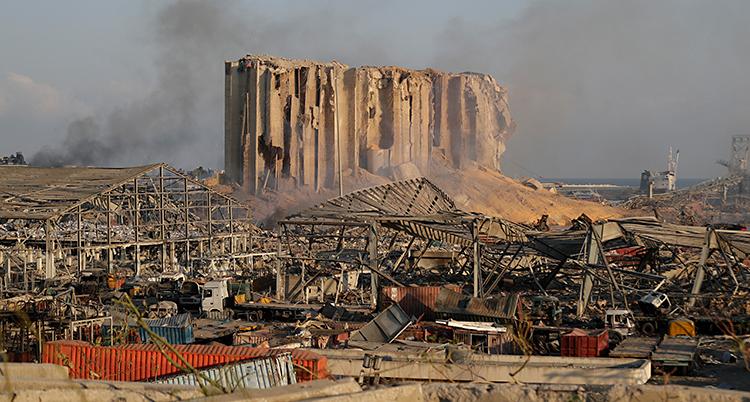 En stor byggnad är alldeles trasig. Och framför den finns förstörda hus och bilar. Allt ligger i en bråte. Och det ryker från bråten.