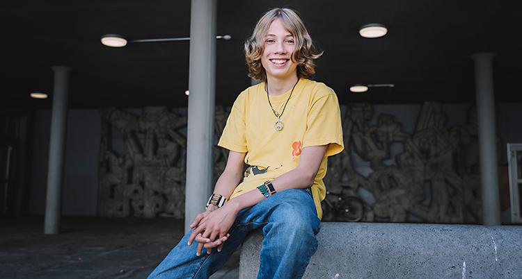 En kille sitter och ler och tittar in i kameran. Han har på sig en gul t-shirt och blå jeans.