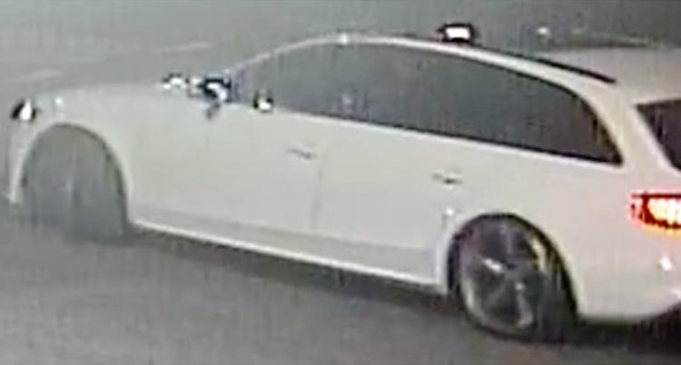 Det är en suddig bild. Kanske är den från en övervakningskamera. Det är en vit bil på bilden, en kombi.