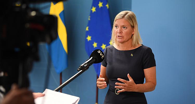 Hon står i ett rum och pratar i en mikrofon. En kamera filmar henne. Hon har blont hår. I bakgrunden är en blå vägg. Vid väggen finns Sveriges flagga och EUs flagga.