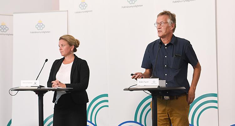 Två personer står på en scen. De har varsitt bord som de står vid. De har varsin mikrofon. Kvinnan står till vänster och mannen till höger.