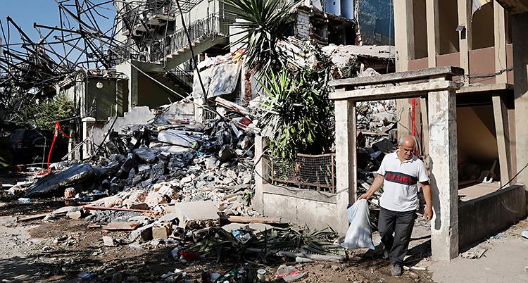 En man går med en säck med sina saker i. Runt om honom finns det hus som är förstörda.