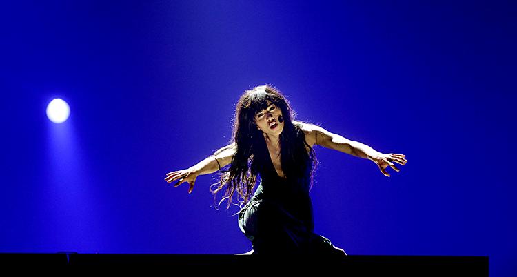 En kvinna är på en scen. Hon har svarta kläder. Det är blått ljus på scenen.