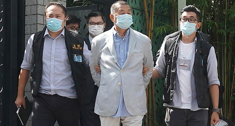 En man blir gripen av poliser. Han är ungefär 70 år. Han har en ljus kostym. På varsin sida går en polis som håller om hans arm. Alla har munskydd.