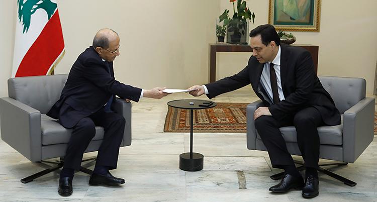 Två män sitter i ett rum. De sitter på varsin stol. Båda har kostym. Mannen som sitter till höger sträcker över ett papper till mannen till vänster.