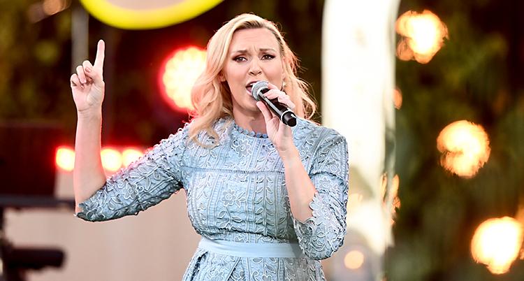 Hon står på en scen och sjunger. Hon håller en mikrofon med ena handen. Med andra handen pekar hon i luften med sitt pekfinger. Hon har en ljusblå klänning och blont hår.