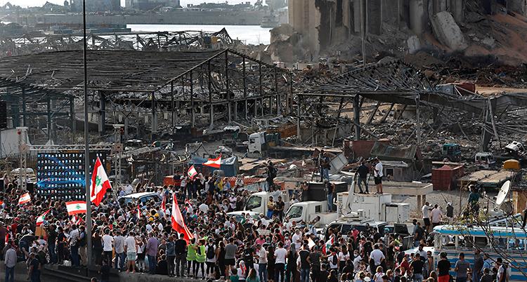 Många människor är samlade utomhus. Flera har Libanons flagga. I bakgrunden står en stor byggnad som är förstörd. Det var där som explosionen hände.