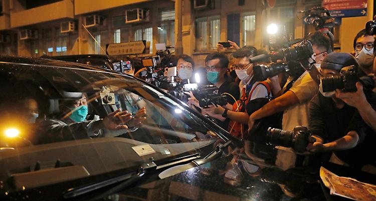 Vi ser en bil på en gata i Hongkong. En äldre man med munskydd sitter i bilen. Runtom står en massa människor med kameror för att filma och fotografera honom.