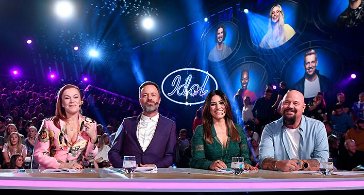 Bilden är tagen i en tv-studio. Fyra personer sitter bakom ett slags skrivbord. De tittar in i kameran. I bakgrunden syns en massa publik.