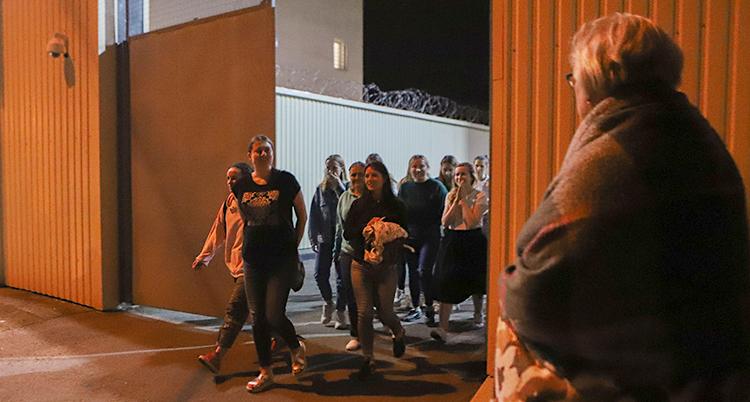 Bilden visar flera unga kvinnor som kommer ut genom en stor port. Runt byggnaden är det taggtråd.