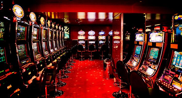 Det är ett mörkt rum med röda lampor. I rummet finns det en massa spelmaskiner. Framför varje maskin finns en pall att sitta på.
