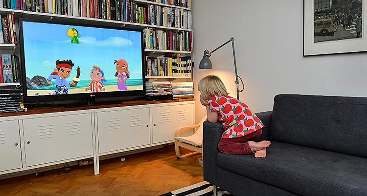 Bilden är tagen i ett vardagsrum. Ett barn sitter i en soffa och tittar på tv. Det är tecknat barnprogram på tv.